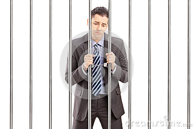 Handcuffed businessman in suit posing in jail and holding bars