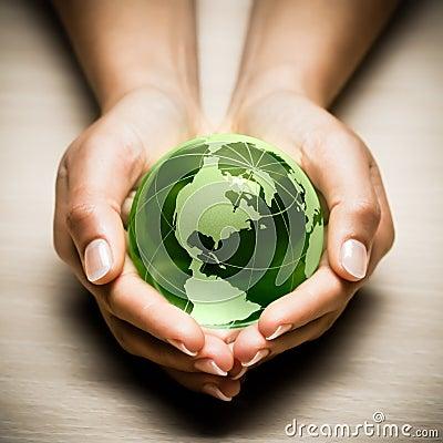 Handen met de groene bol van de Aarde