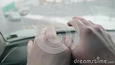 Handen van de mens op het stuur van de auto Man houdt stuurwiel op een vreemde manier vast stock videobeelden