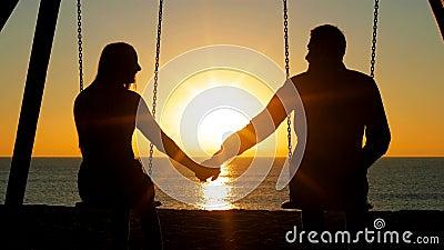 Handen van de paar de slingerende holding bij zonsopgang stock footage
