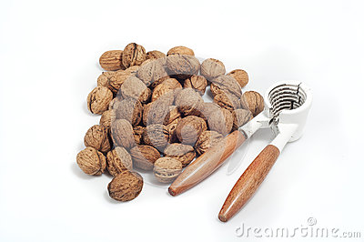 Handful of walnuts on white background, with a nutcracker
