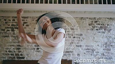 Handheld av glad afrikansk amerikanteeangerflicka ha near säng för rolig dans hemma arkivfilmer