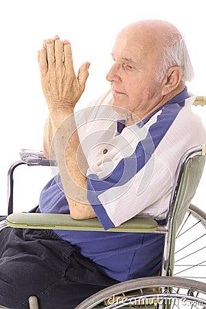 Handicap senior praying in wheelchair