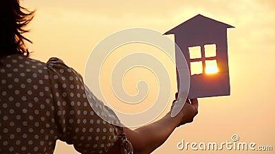 Handje met een papieren huismodel tegen zonsondergang Gefeliciteerd familieconcept, bouw en vastgoedtransacties stock video