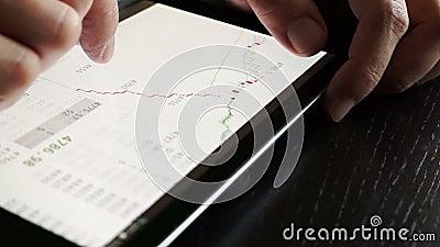 Handlowiec używa pastylkę dla sprawdzać akcyjnych dane zbiory