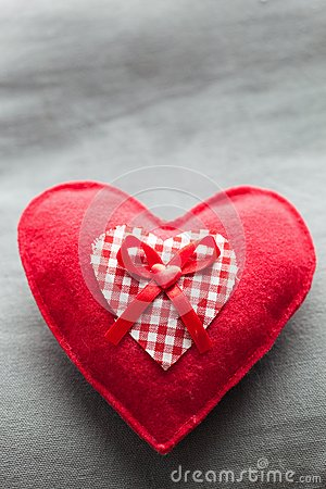 Handmade plush red heart on the soft pillow