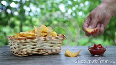 Hands of adult female taking potato chips from wickered bowl and dipping them in ketchup stock footage
