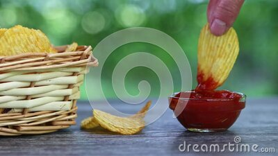 Hands of adult female taking potato chips from wickered bowl and dipping them in ketchup slow motion stock video footage