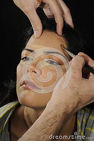 Hands applying make up on hispanic girl