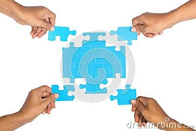 Hands assembling puzzle.