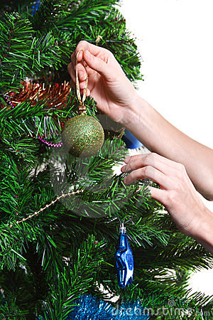 Hands with ball adorning chritmas tree