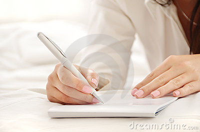 Hands of a beautiful young woman writing on a pad