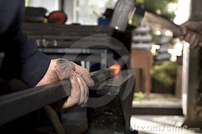 Hands of blacksmith by the work