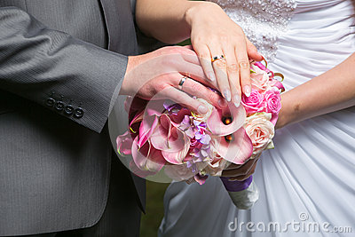 Hands of bride and groom on wedding bouquet