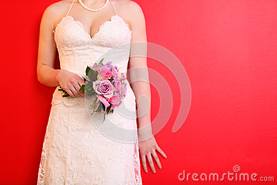 Hands of bride wearing dress hold bouquet