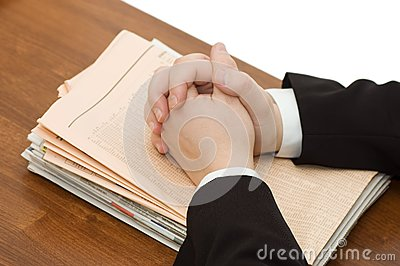 Hands of the businessman on a pile of newspapers