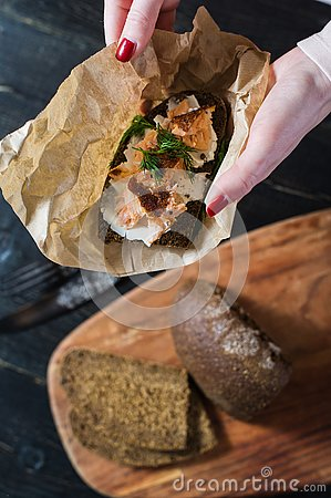 The hands of the chef holding the Scandinavian sandwich with smoked salmon on black bread with soft cheese Stock Photo