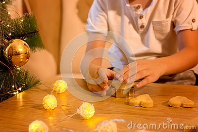 Hands of a child making ginger cookies in the shape of a heart. Stock Photo