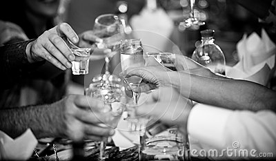Hands clinking glasses with vodka at party