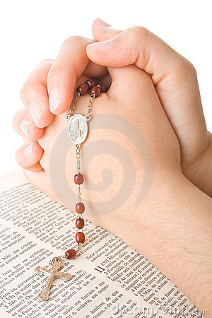 Hands closed in prayer with a rosary