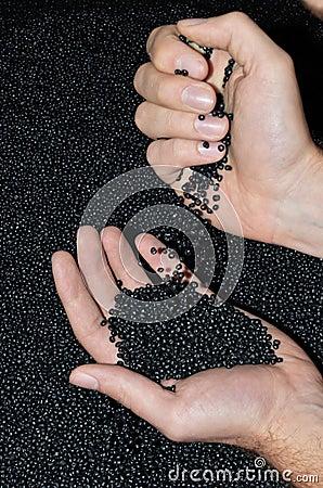 Hands dumping polymer resin