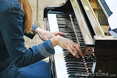 Hands gently playing a melody on the piano