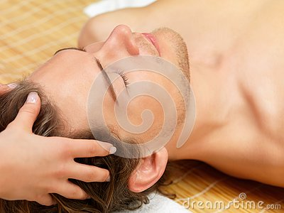 Hands giving young man a face massage