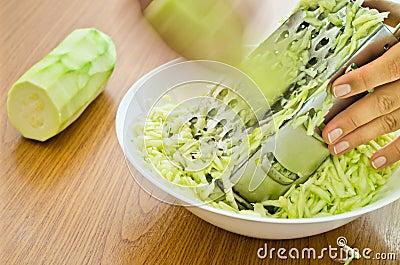 Hands grating zucchini