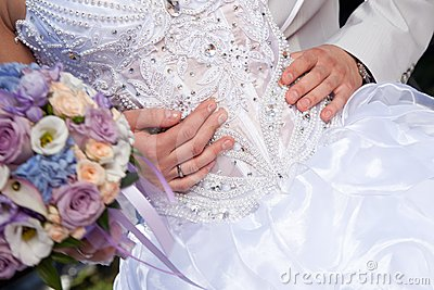 Hands of groom gently embracing brides s waist