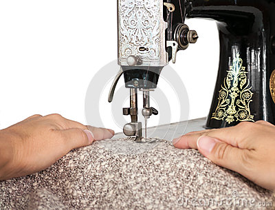 Hands guiding fabric through a vintage sewing machine
