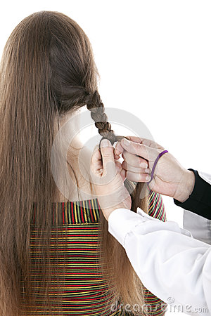Hands of hairdresser doing a braid a long mane