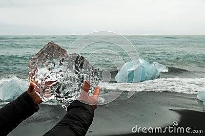 Hands holding a block of pristine glacier ice