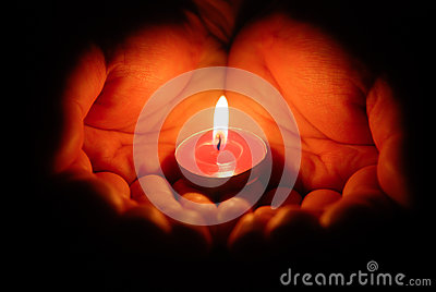 Hands holding a burning candle