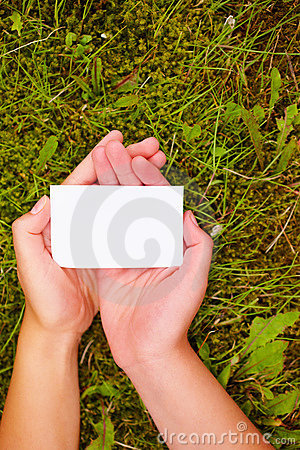 Hands holding a business card isolated over grass