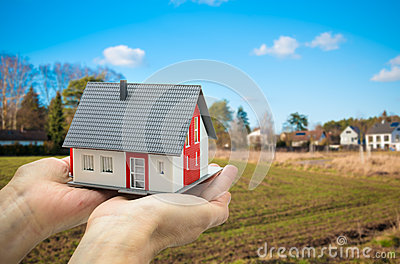 Hands holding a house model