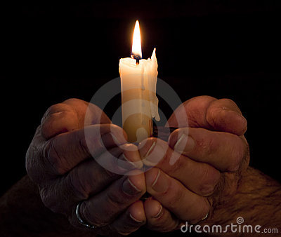 Hands holding lighted candle in darkness