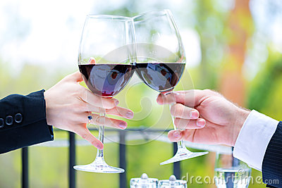 Hands holding red wine glasses to clink