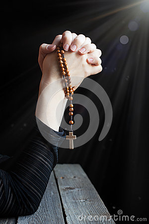 Hands holding rosary with a cross and folded in prayer in the ra