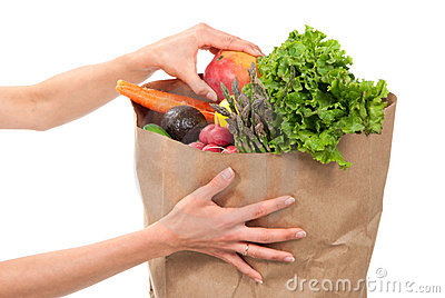 Hands holding shopping paper bag full of groceries