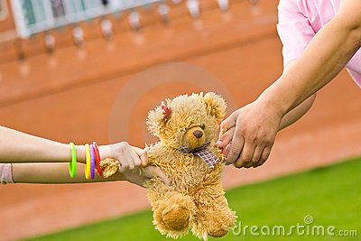 Hands holding small teddy bear