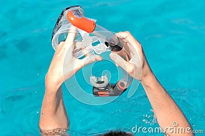 Hands holding snorkel gear