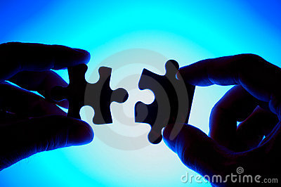 Hands joining two puzzle pieces.