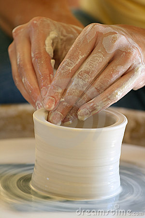 Hands making pottery