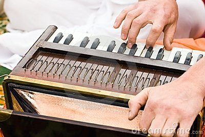 Hands of man playing mantra on accordion
