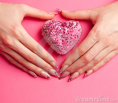 Hands with manicure folded in the shape of heart
