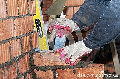 Hands of a mason at bricklaying