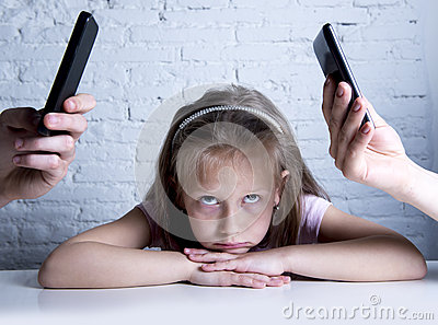 Hands of network addict parents using mobile phone neglecting little sad ignored daughter bored Stock Photo
