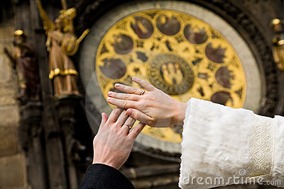 Hands of newly married on clock background