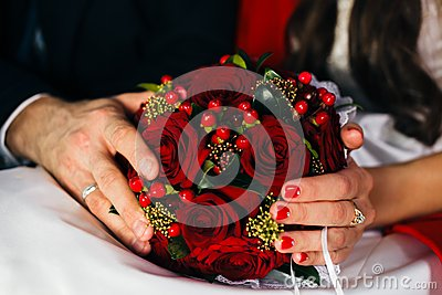 Hands of newlyweds holding a wedding bouquet
