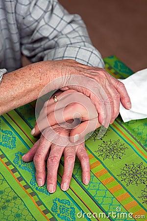 Hands of a nurse and a former senior